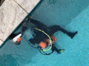 man in scuba gear looking for leaks in pool
