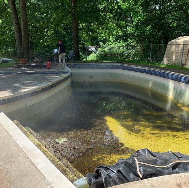 Backyard pool with dirt and algae on bottom